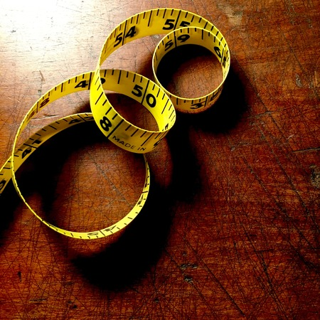 Yellow tape measure on wood background