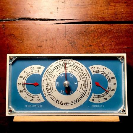 Vintage blue barometer on weathered wood background.