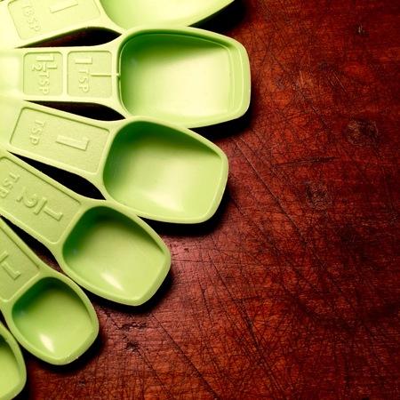 Vintage green measuring spoons on wood table. Reklamní fotografie