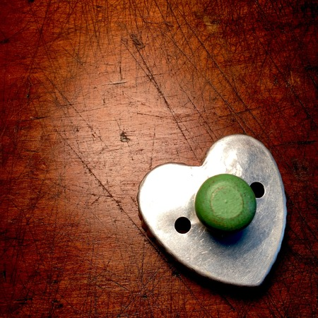 Vintage heart shaped cookie cutter with green wood handle. Reklamní fotografie