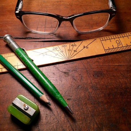 Ruler, writing utensils and spectacles on wooden desktop. Reklamní fotografie