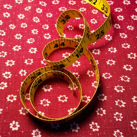 Tape measure on red fabric background