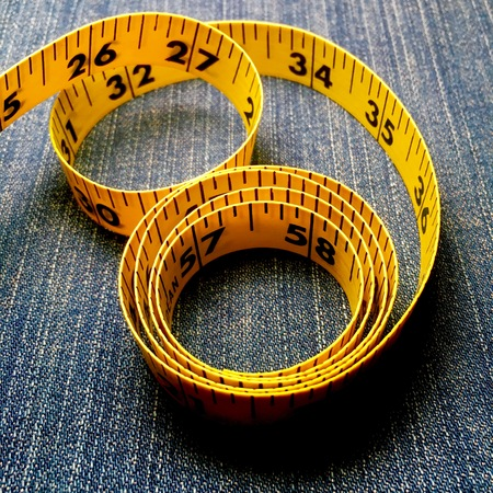 Yellow tape measure on denim background