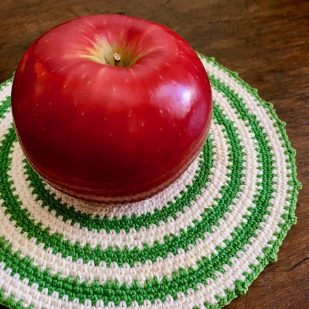 Apple and crocheted doily on wood table