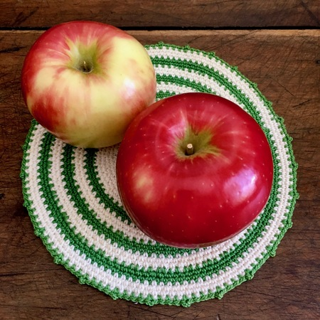 Apples and crocheted doily on wood table