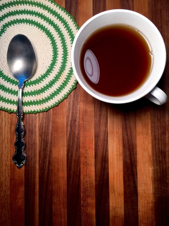 Hot beverage with vintage doily and spoon