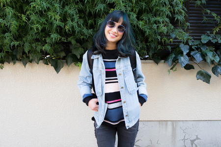 Asian model with green and blue streaks in her hair and sun glasses in a light denim jacket