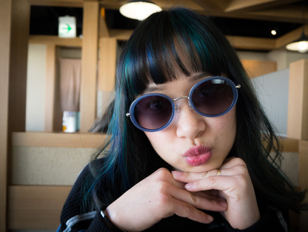 Asian model with green and blue streaks in her hair posing with trendy sunglasses