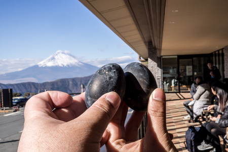 Black eggs cooked in the sulfur of Mount Hakone and sold in Owakudani shops with Mount Fuji in the background Editorial