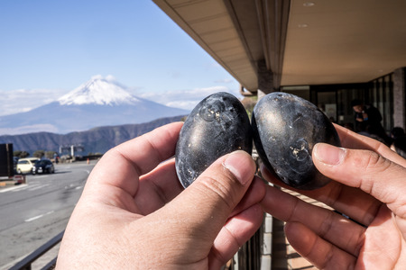 Black eggs cooked in the sulfur of Mount Hakone and sold in Owakudani shops with Mount Fuji in the background Banco de Imagens