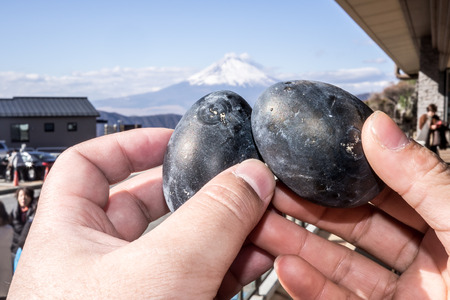 Black eggs cooked in the sulfur of Mount Hakone and sold in Owakudani shops with Mount Fuji in the background Foto de archivo