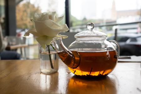 White rose next to fancy tea pot