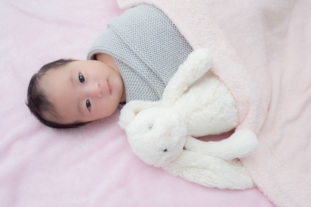 4 weeks old newborn baby wrapped in grey blanket 版權商用圖片