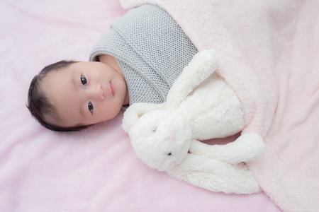 4 weeks old newborn baby wrapped in grey blanket Standard-Bild