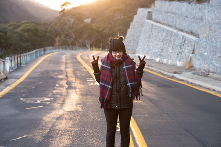 Young woman posing on the road at the crack of dawn with a beautiful sunrise