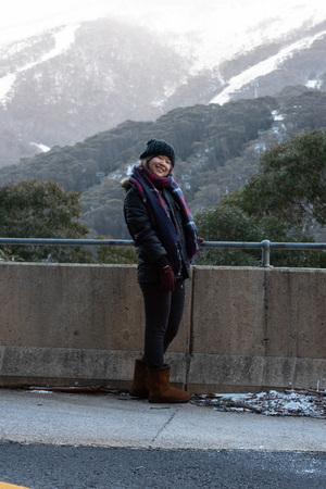 Young woman posing in front of snow covered Mount Kosciuszko at Thredbo