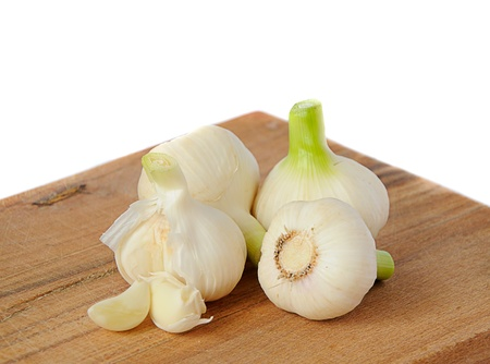 fresh garlic on wooden board and white background