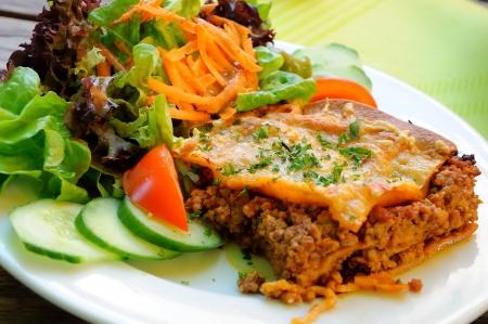 lasagna with mixed salad and tomato