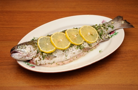 fresh rainbow trout with spices and lemon ready for coocking