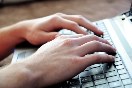 hands typing on laptop keyboard Stock Photo