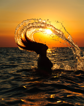 silhouette of a girl splashing water with hair