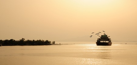 ferry boat on suunset and seagulls Stock Photo