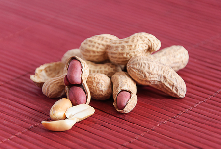Peanuts in shels on violet pad, stock photo