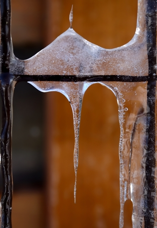 Icicles on a rusted fence