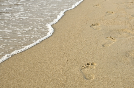 footprints on the sand and sea wave Stock Photo