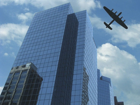 Perspective view of glass skyscraper with Lancaster heritage warplane flying in blue sky with clouds
