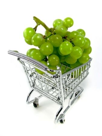 Bunch of green grapes in chrome shopping cart  isolated on white background