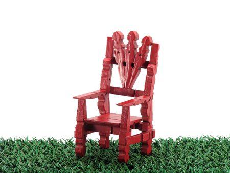 Red clothespin zabawka krzesło na zielonej trawie wyizolowanych na białym tle.