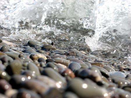Wave running over glistening pebbles Stock Photo
