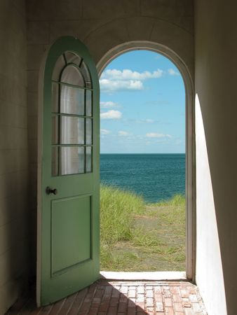 Arched doorway opening onto a grassy beach with sunlight streaming in.