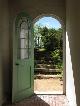 Arched doorway opening on stone garden stairs with sunlight streaming in.