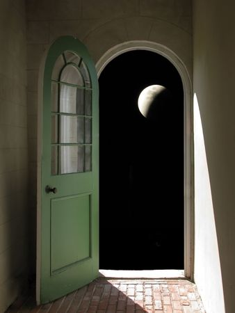 Arched doorway opening on night sky with large moon