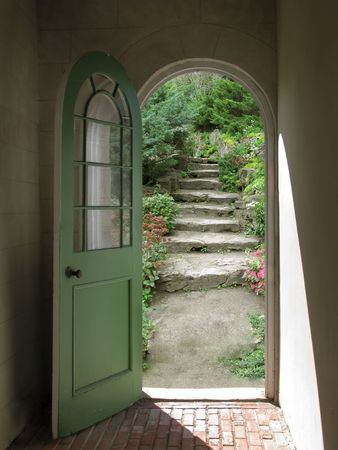 arched: Arched doorway opening on stone garden stairs with sunlight streaming in.