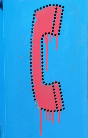 Red painted graffiti on blue phone booth