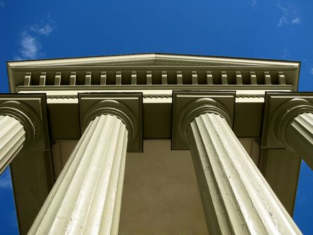 Looking up at sturdy columns on classic building with blue sky