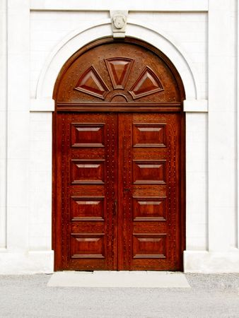 Large wooden door with arched top in white stone wall Stock Photo