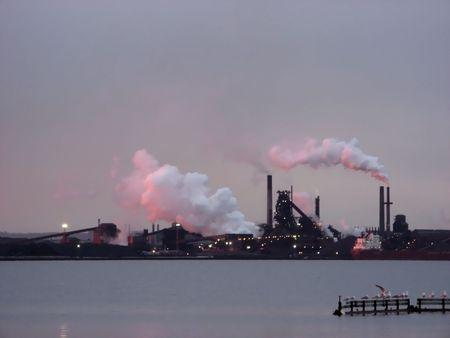 Kompleks przemysłowy nad wodą z billowing chmury pary odzwierciedlających sunrise
