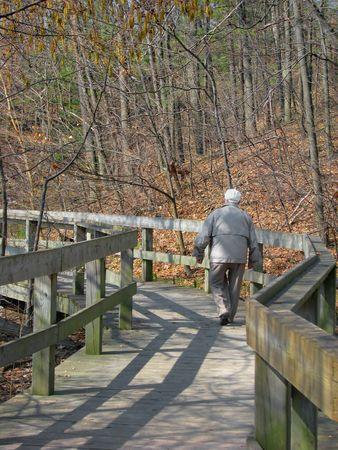 Senior citizen walking on boardwalk