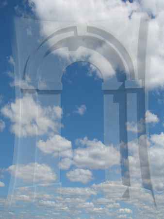 Distorted arched stone doorway fading into blue sky with clouds