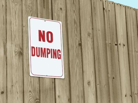 Sign posted on wooden fence