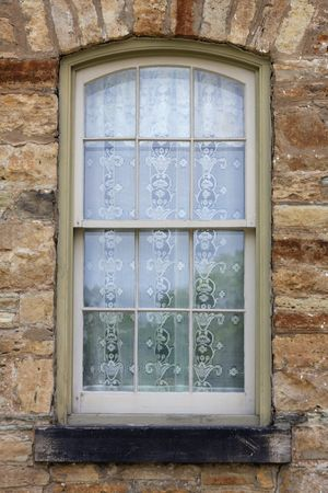 Detail view of window in rough stone wall with lace curtains Stock Photo