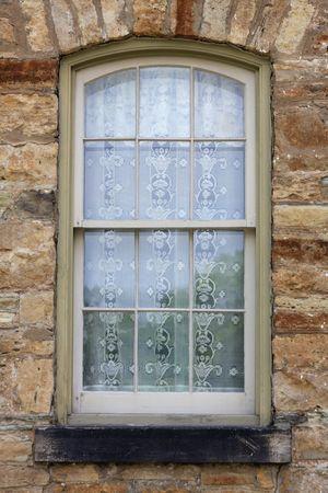 Szczegóły widok okna w nieobrabiane kamiennym murem z koronki zasłony