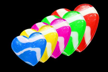 Neon colored candy hearts isolated on black background photo