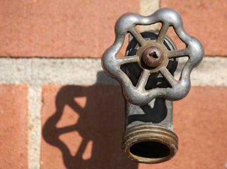 Closeup view of backyard faucet on brick wall Stock Photo