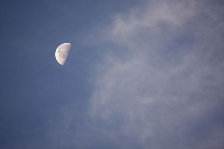 Half moon in blue sky with whispy clouds Stock Photo