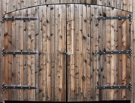 Pair of large wooden arched doors with old fashioned hinges